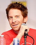 A man with red hair, smiling slightly and sitting behind a microphone.