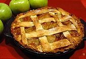 An apple pie on a red table cloth, with green apples next to it.