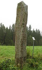 A vertical inscribed stone rising from gras with treest in the background.