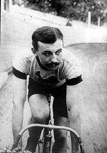 A man on a bicycle with shorts, short sleeves, racing on a velodrome.