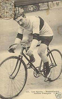 A postcard of a man on a bicycle looking at the camera.