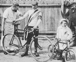 A black and white photograph of a man holding his bicycle and a little boy with a little bicycle, being looked upon by two other men.